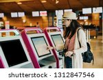 Small photo of Young Asian travel woman using self check-in kiosks in lobby. Technology in airport. female photographer with backpack and luggage touching monitor of auto machine to make sure her flight timetable