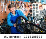 man seller in uniform repairing ... | Shutterstock . vector #1313105936