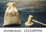Small photo of Money bag with the word Fine and the judge's hammer. Penalty as a punishment for a crime and offense. Financial punishment. Violations of traffic laws. Fraud. Fines can also be used as a form of tax