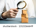 Small photo of A man holds a magnifying glass above the boxes. Examination of goods for the presence of contraband, prohibited goods, defects. Quality control, authentication. study of consumer sentiment