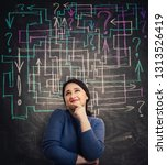 Small photo of Puzzled young woman in front of blackboard with different colorful arrows try to solve a question maze and find the answer. Problem analysis solution concept with exclamation and interrogation marks.