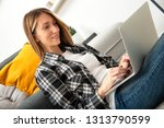 young woman using laptop on... | Shutterstock . vector #1313790599