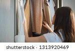 young woman choosing clothes in ... | Shutterstock . vector #1313920469