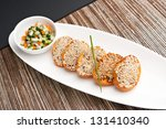 Thai or Asian style shrimp sesame toasts with garnish and cucumber salad. - stock photo