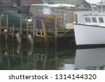 lobster traps on dock and boat... | Shutterstock . vector #1314144320