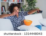 black woman watching tv at home ... | Shutterstock . vector #1314448043