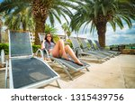 woman on a lounger by the pool... | Shutterstock . vector #1315439756