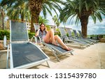 woman on a lounger by the pool... | Shutterstock . vector #1315439780