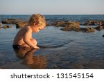 A Little Boy Sits In The Water...
