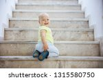 baby girl crawling up stairs... | Shutterstock . vector #1315580750