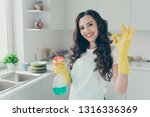 Small photo of Close up photo beautiful busy nice duties she her lady house hold okey symbol washing supplies pulverize promo housemaid wear jeans denim casual t-shirt covered by cute apron bright light kitchen