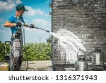 Brick House Wall Pressure Washing with Special Cleaning Detergent. Caucasian Men in His 30s. Taking Care of the Building Elevation. - stock photo