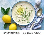 Small photo of Avgolemono - traditional greek chicken soup with orzo pasta, eggs and lemon in a vintage bowl over light blue slate, stone or concrete background.Top view with copy space.