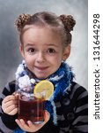 Happy little girl with large cup of hot lemon tea wearing warm clothes - stock photo