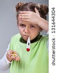 Sick little girl with the flu - holding pills and thermometer - stock photo