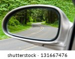 Side view mirror reflection of two-lane winding road in forest - stock photo