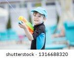 cute young boy shooting water... | Shutterstock . vector #1316688320