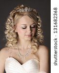 Young beautiful woman dressed as a bride on a gray background. - stock photo