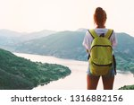 a young girl stands on a rock...   Shutterstock . vector #1316882156