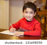 Little Boy Sitting At A Table...
