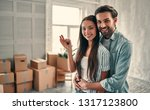 Small photo of Couple on moving day. Attractive young woman and handsome bearded man with cardboard moving boxes are happy to move into new home.