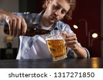 depressed young man drinking... | Shutterstock . vector #1317271850
