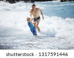father and son playing on the... | Shutterstock . vector #1317591446