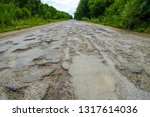 bad road  cracked asphalt with... | Shutterstock . vector #1317614036