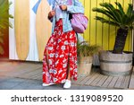 Fashion details of stylish woman posing near beach cafe, USF boards and palms trees, wearing hipster outfit, maxi floral feminine skirt, denim jacket and backpack, summer spring travel vibes.