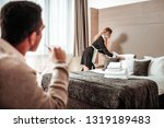 Small photo of Behaving immoral. Dark-haired businessman behaving immoral while watching hotel maid working