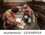 Small photo of Inattentive woman. Inattentive stylish blonde-haired woman dropping documents on the floor in elevator
