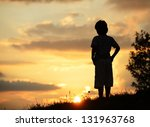 Active kid spending time on summer meadow by sunset - stock photo