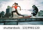 Small photo of Female athlete training on terrace of a building with a parachute tied behind her. Fitness woman running hard with a drag parachute on rooftop with sun flare in the background.