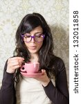 Woman At Home Blowing On Cup O...