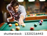 serious man aiming at pool ball ... | Shutterstock . vector #1320216443