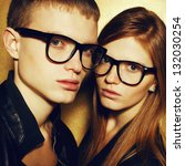 Portrait of gorgeous red-haired fashion twins in black clothes wearing trendy glasses and posing over golden background together. Perfect hair. Natural make-up. Perfect skin. Vogue style. Close up - stock photo