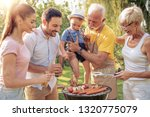family having a barbecue in the ... | Shutterstock . vector #1320775079