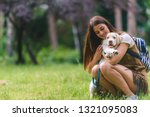 Stock photo beautiful young woman playing with a puppy labrador in the park 1321095083