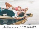 happy couple of surfers lying... | Shutterstock . vector #1321569419