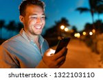 man smiling looking at phone... | Shutterstock . vector #1322103110