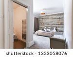 Small photo of En-Suite Modern Bedroom with rustic wooden headboard and white linen and pillows, copper lamp shade - Airbnb accommodation