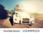 group of happy friends in a car ... | Shutterstock . vector #1323499223