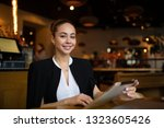 Small photo of Portrait of a happy smiling woman professional hostess holding touch pad in hands and looking in camera, sitting in restaurant interior. Beautiful female business owner using digital tablet