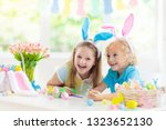 kids dyeing easter eggs.... | Shutterstock . vector #1323652130