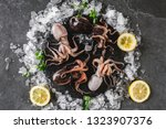 fresh raw baby octopuses with... | Shutterstock . vector #1323907376