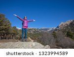hiker woman on rock  with arms... | Shutterstock . vector #1323994589