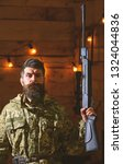 Small photo of Gamekeeper concept. Hunter, brutal hipster with gun in his hand ready for hunting. Macho on strict face at gamekeepers house. Man with beard wears camouflage clothing in wooden interior background.
