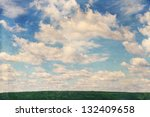 Spring field against the sky with clouds, vintage - stock photo