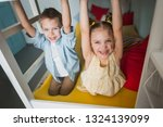 cute smiling beautiful children of 7-8 years old, a boy and a girl are hanging on the upper level of a bunk bed sitting downstairs, having fun playing