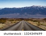 Small photo of USA, California, Inyo County, Death Valley National Park. Daylight Pass Road straightaway above Mud Canyon with the purple majesty of the Funeral Mountains looming in the distance.